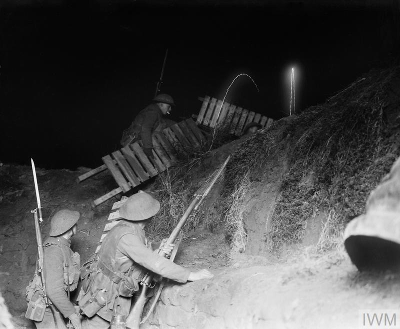 British Army fatigue party carrying duck boards over a support line trench at night. Cambrai, 12 January 1917.