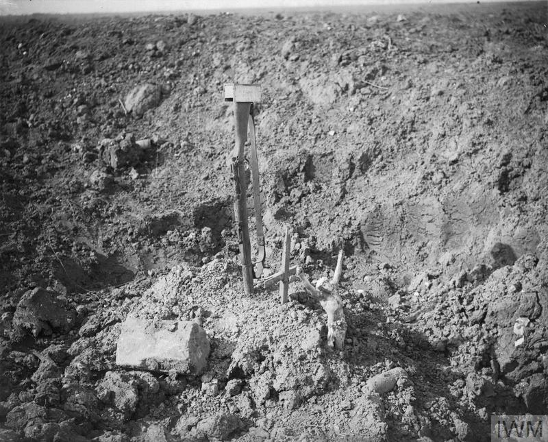 A makeshift grave in a shell-hole, marked by an inverted rifle driven into the ground near Combles.