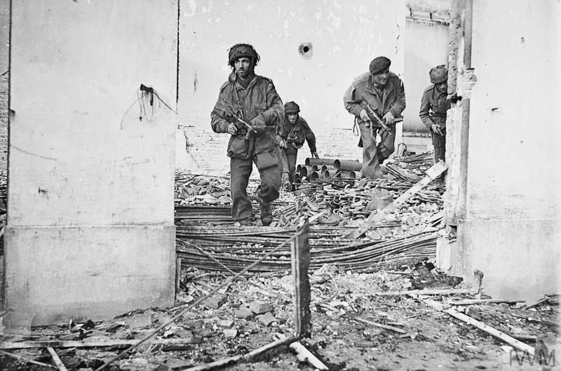Posed photo of British airborne troops moving through a shell-damaged house in Oosterbeek, 23 September 1944.