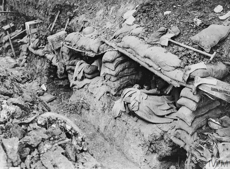 Men resting in sleeping shelters dug into the side of a trench near Contalmaison.