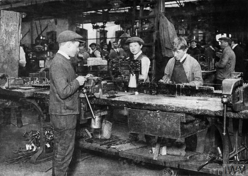 Boys assembling switch gears at an aircraft factory.