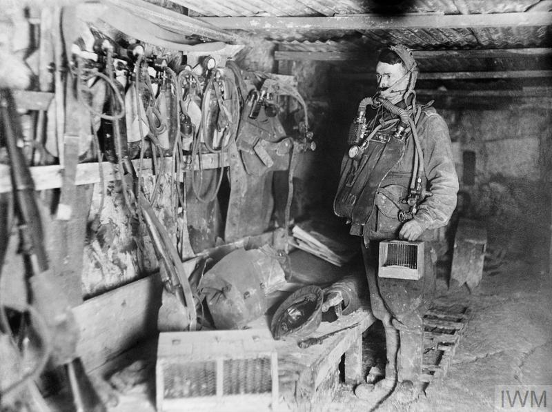 The interior of 3rd Australian Tunnelling Company's Mine Rescue Station at Hulluch, near Loos, France, 31 January 1918. The sapper wears the 'Proto' breathing apparatus and carries a small cage containing a white mouse or canary for testing the air conditions underground.