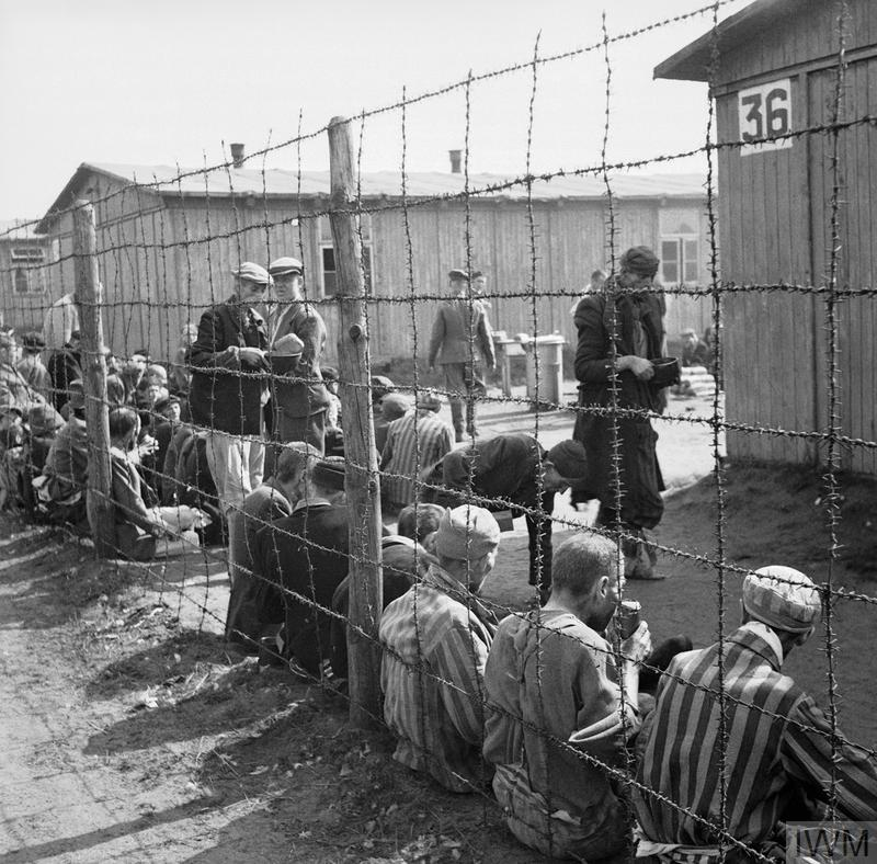 Prisoners sit by the wire fence dividing the various sections of the camp. They are eating their first meal after the liberation of the camp.