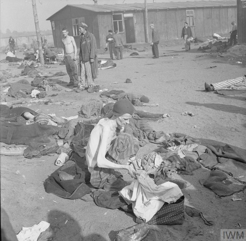 A camp inmate, reduced by starvation to a living skeleton, delouses his clothes, 17-18 April 1945
