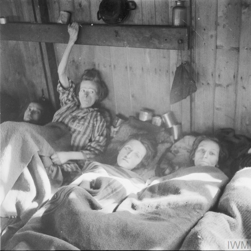 Three women who are suffering from typhus lie closely packed together in one of the huts.