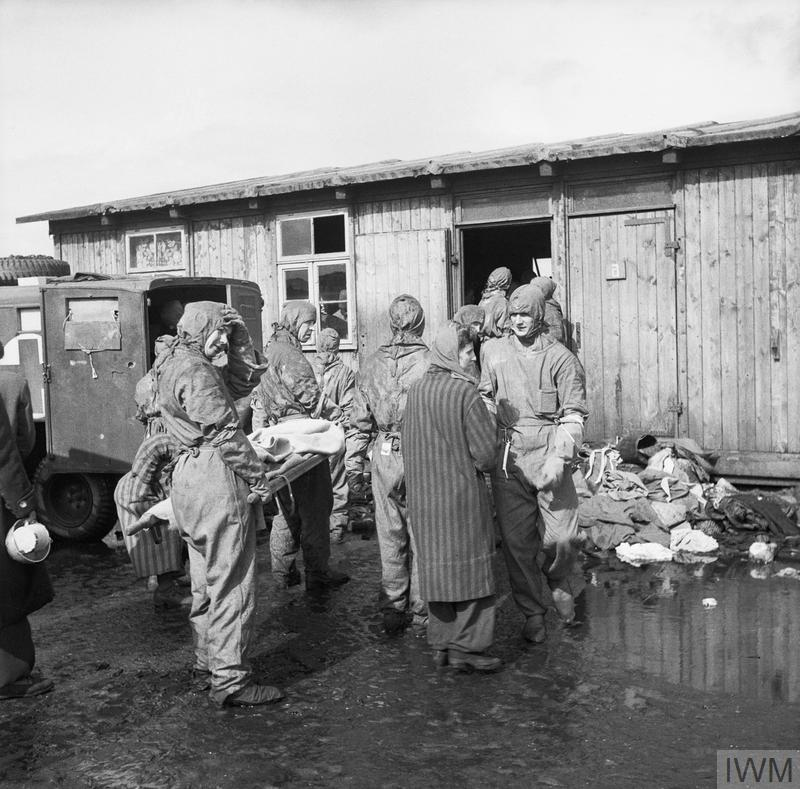 Wearing protective clothing, men of 11 Light Field Ambulance, Royal Army Medical Corps evacuate inmates from one of the huts at Belsen.