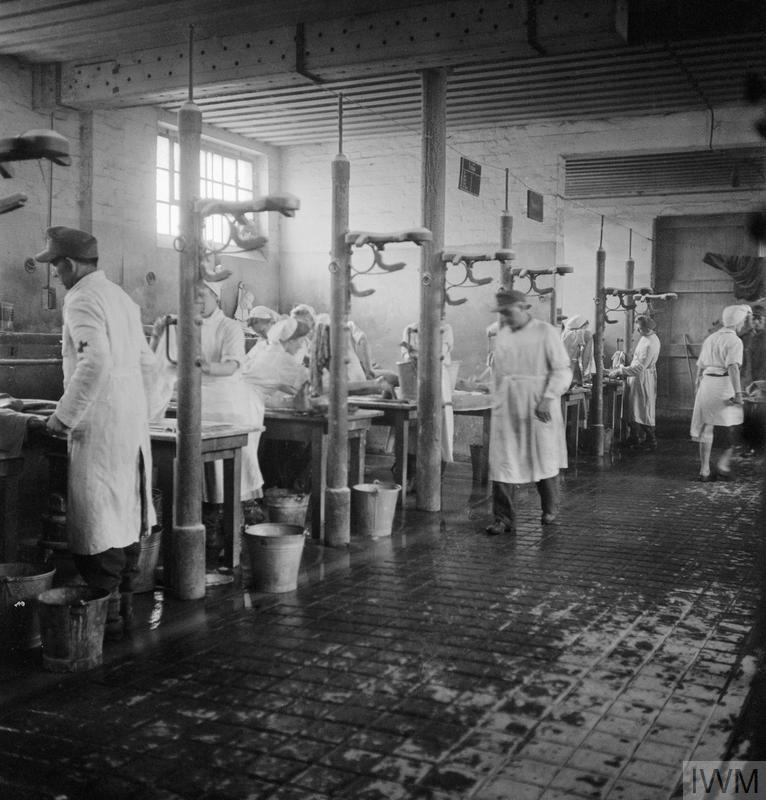 "Scene inside the cleansing station, nicknamed the ""Human Laundry"", which was housed in a former stable for cavalry horses at the newly established hospital for Belsen inmates in Hohne Military Barracks. The photograph shows some of the 60 tables, each staffed by two German doctors and two German nurses, at which the sick were washed and deloused."