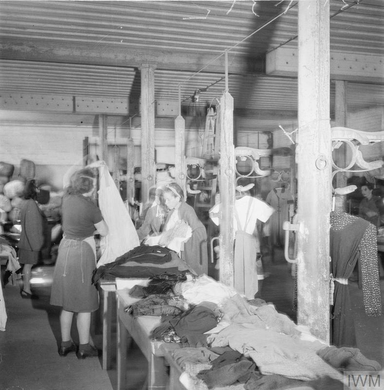 Women at Belsen selecting new items of clothing from supplies provided by UNRRA and by a levy on the local population. Mrs H Tanner, an UNRRA relief worker from Grantham, assists inmates select a dress.