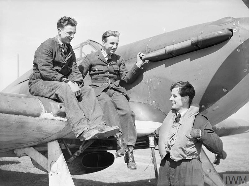 British Personalities: Squadron Leader Peter Townsend DSO DFC chatting with ground crew who are seated on his Hawker Hurricane at Wick, Scotland.