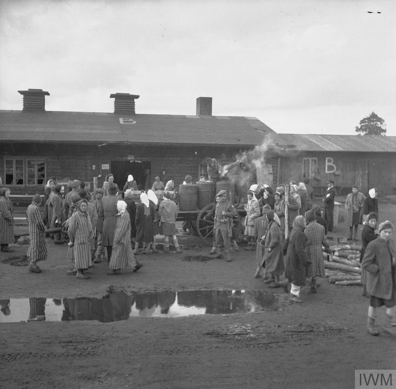 British soldiers supervise the distribution of food to camp inmates.