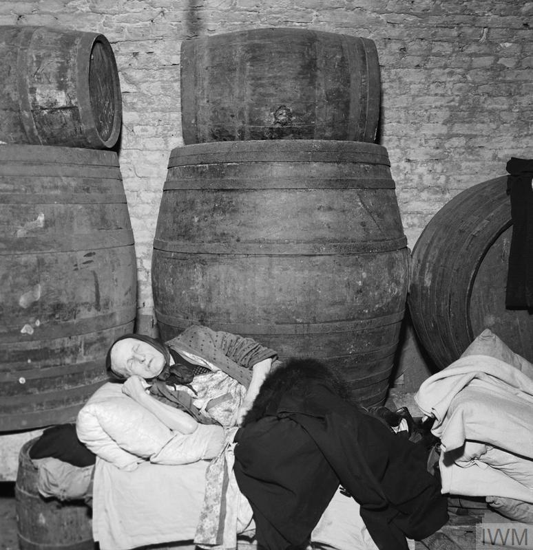 East End Wine Merchant's Cellar: Old woman sleeps in a bed constructed on top of a row of barrels.