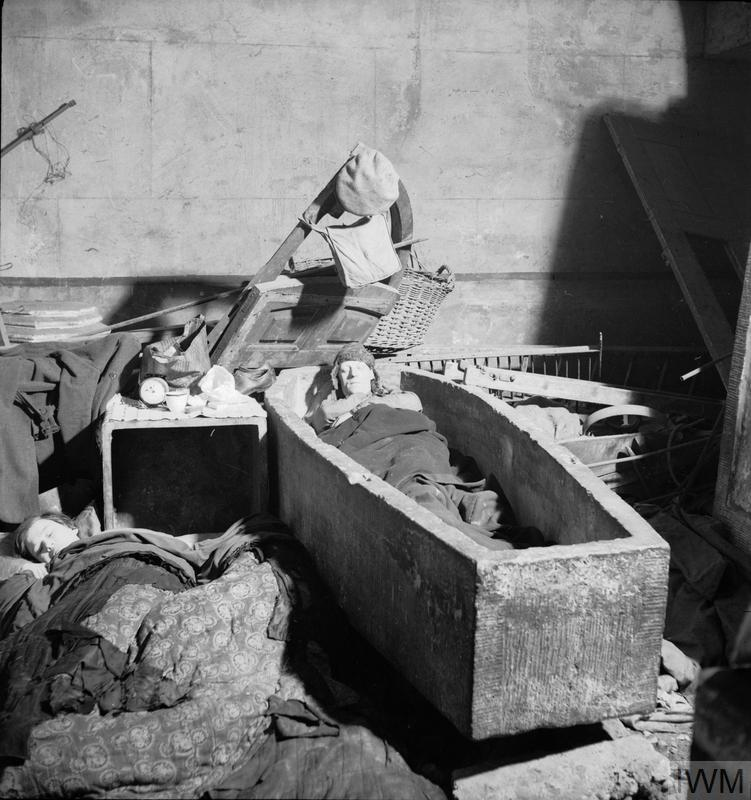 A man sleeping in a stone sarcophagus in an East London church in November 1940.