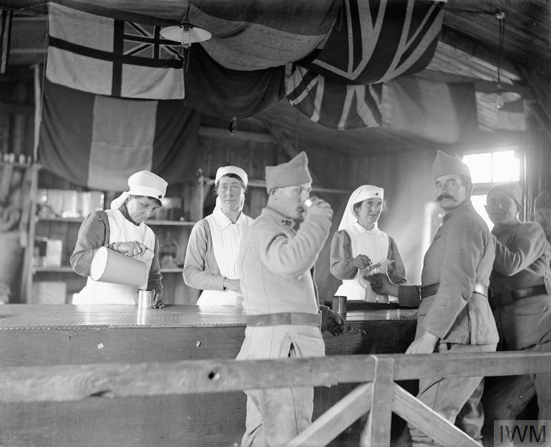 Three French soldiers at the bar of a French Red Cross Canteen with British staff at Compiegne.