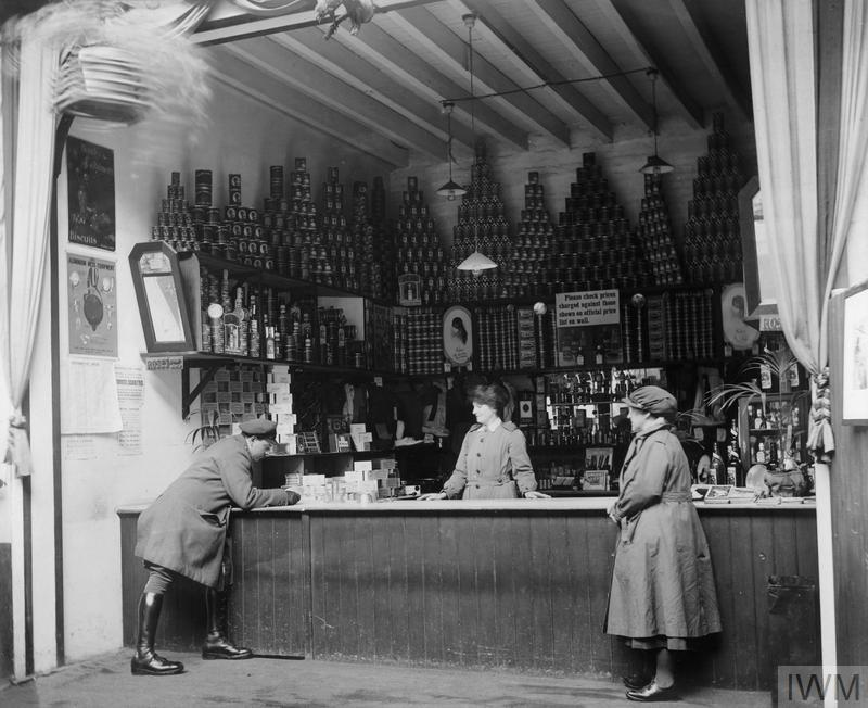The well stocked shelves of the Officers Expeditionary Force Canteen in Le Havre with a member of the Queen Mary's Army Auxiliary Corps (QMAAC) behind the counter and another colleague and a young lieutenant in front.