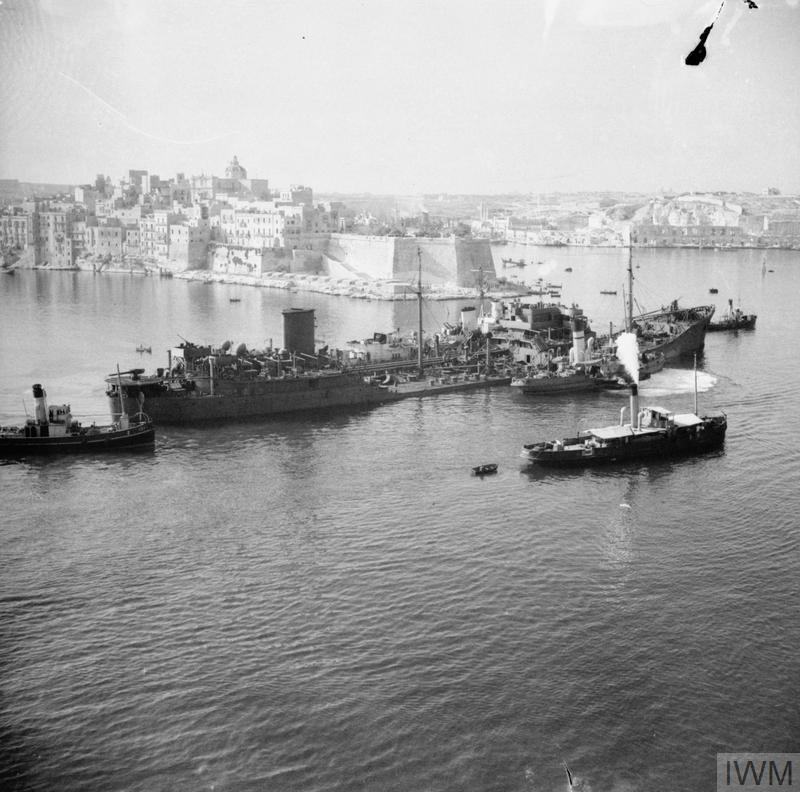The damaged tanker OHIO, supported by Royal Navy destroyers, approaches Malta after an epic voyage across the Mediterranean as part of convoy WS21S (Operation Pedestal) to deliver fuel and other vital supplies to the besieged island. OHIO's back was broken and her engines failed during heavy German and Italian attacks. Because of the vital importance of her cargo (10,000 tons of fuel which would enable the aircraft and submarines based at Malta to return to the offensive), she could not be abandoned.