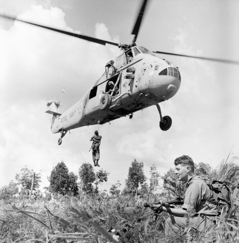 While operating in Borneo during the Indonesian Confrontation, a soldier is winched up to a Westland Wessex HAS3 of 845 Naval Air Squadron, during operations in the jungle. A soldier is kneeling on the edge of the extraction zone.