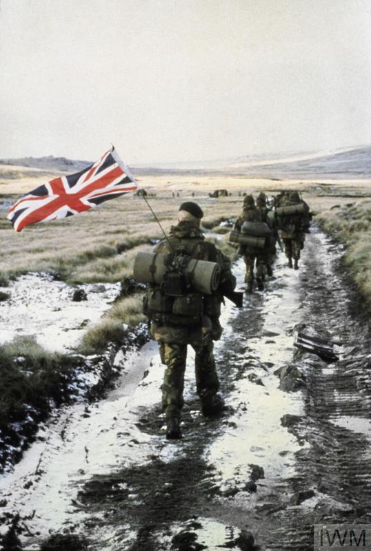 Commandos from 40 Commando Anti-Tank Troop march towards Port Stanley in amongst a column of from 45 Commando (the unit to which they were attached). Royal Marine Peter Robinson, carrying the Union Flag attached to the aerial of the radio he is carrying, brings up the rear. The flag was owned by Marine John 'Snowy' Snowden who was unable to attach the flag to his backpack so he passed it to Robinson.