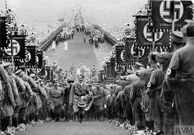 Hitler, flanked by the massed ranks of the Sturm Abteilung (SA), ascends the steps to the speaker's podium during the 1934 harvest festival celebration at Bückeburg.