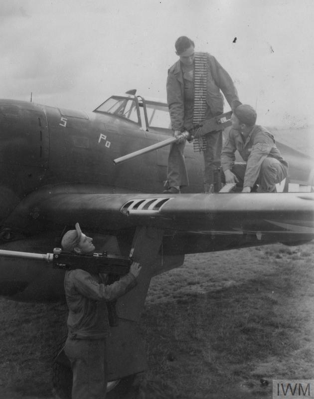 © IWM [FRE 261] Ground crew armourers restore newly-cleaned machine guns to a P-47 Thunderbolt at Duxford, August 1943.