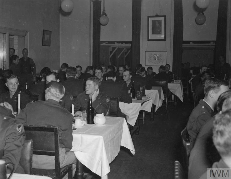 © IWM [FRE 281] - Officers of the 78th Fighter Group sit down to eat in the Officer's Club dining room at Duxford. On this occasion the meal was a venison steak dish, a gift to the unit by a British landowner