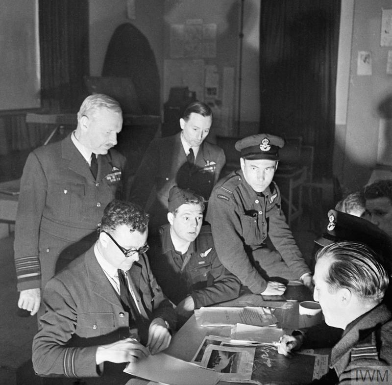 Debriefing of Wing Commander Guy Gibson's crew. Squadron Leader Townson, Intelligence Officer, questions, from left to right: Spafford, Taerum and Trevor-Roper. Pulford and Deering are partly hidden. Air Chief Marshal Sir Arthur Harris and the Hon Ralph A Cochrane, Air Officer Commanding the Group, observe.