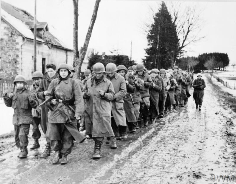 American soldiers being marched down a road after capture by German troops in the Ardennes, December 1944.