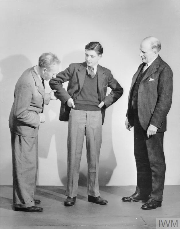 Men trying on clothes from the utility scheme designs, trouser turn-ups had disappeared in the course of economy.