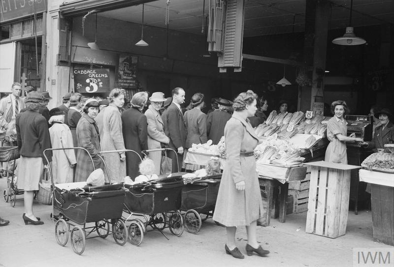 People queuing at a greengrocers in High Road, Wood Green, North London, a familiar wartime sight.