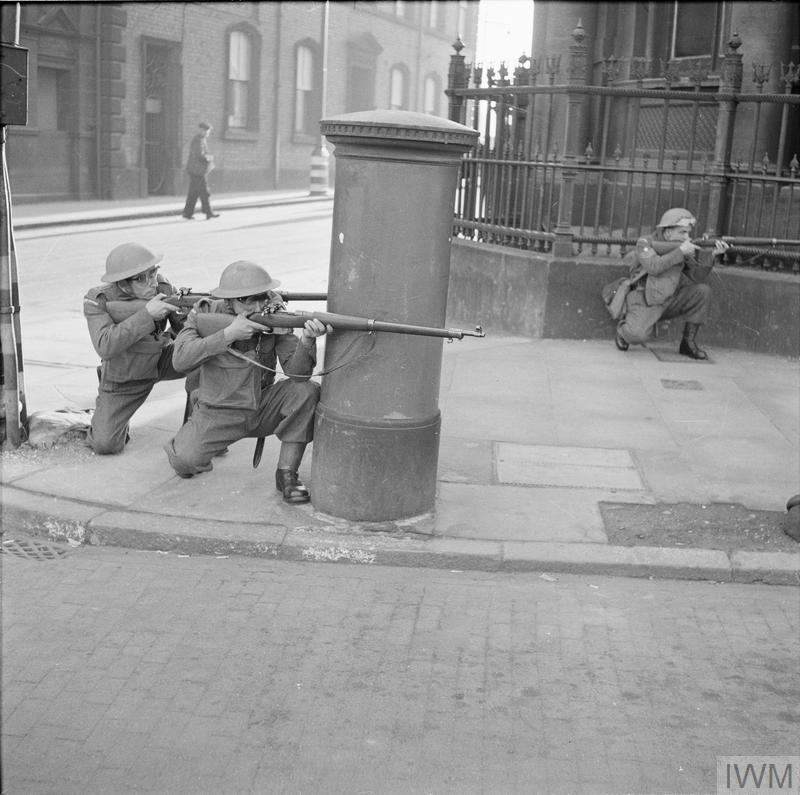 The Home Guard: During an exercise involving the local Home Guard, ARP personnel and the Police in Northen Command, 'enemy' forces succeeded in taking a town after a bitter struggle but were later overpowered. Photograph shows the Home Guard firing at the 'enemy' in the street behind the cover of a post-box.