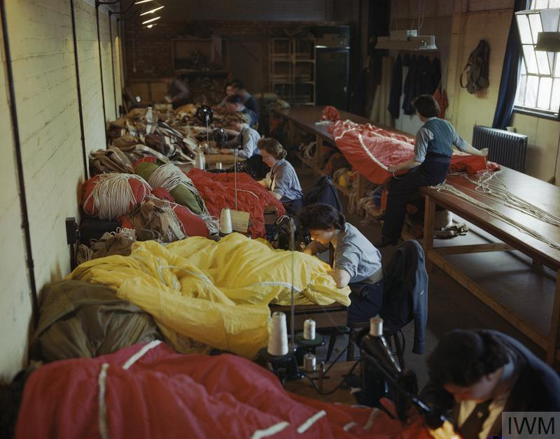 Women's Auxiliary Air Force: WAAF personnel on an RAF glider station in Britain repair and pack coloured parachutes for use by airborne troops during the Normandy invasion.