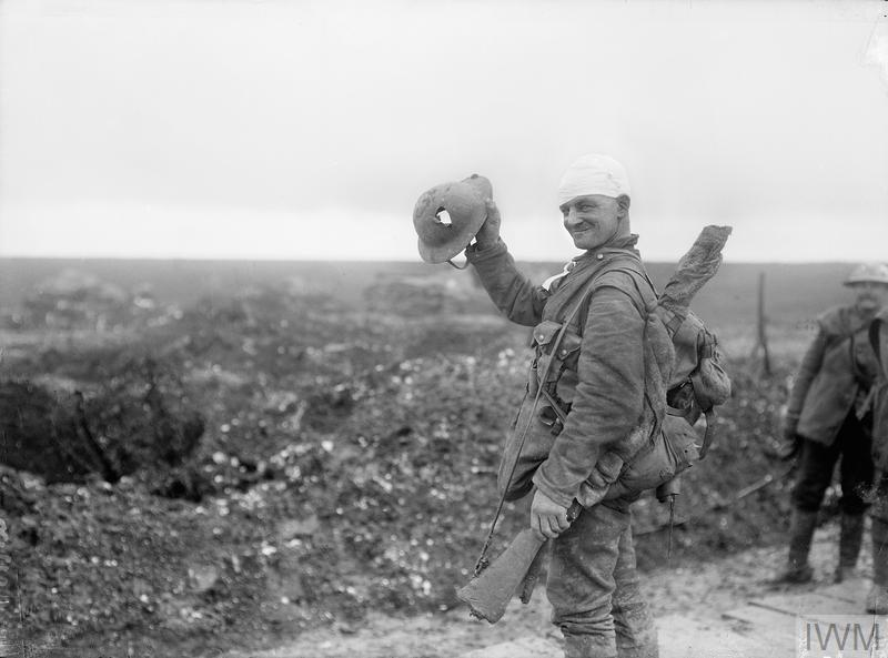 Wounded British soldier holding his steel helmet, which has been pierced by a piece of shrapnel, during fighting on the Somme Front near Hamel in December 1916.