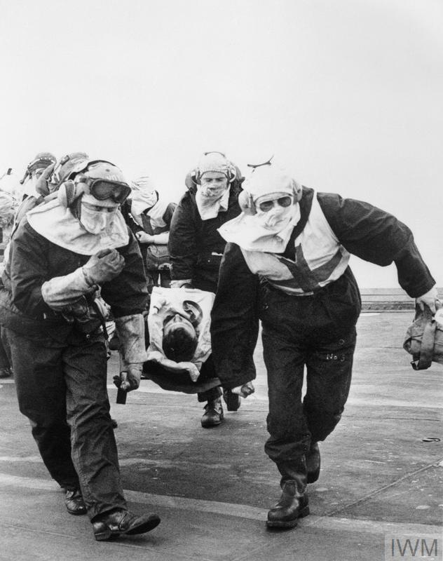 A casualty from HMS SHEFFIELD is rushed by stretcher to Sick Bay on board HMS HERMES.