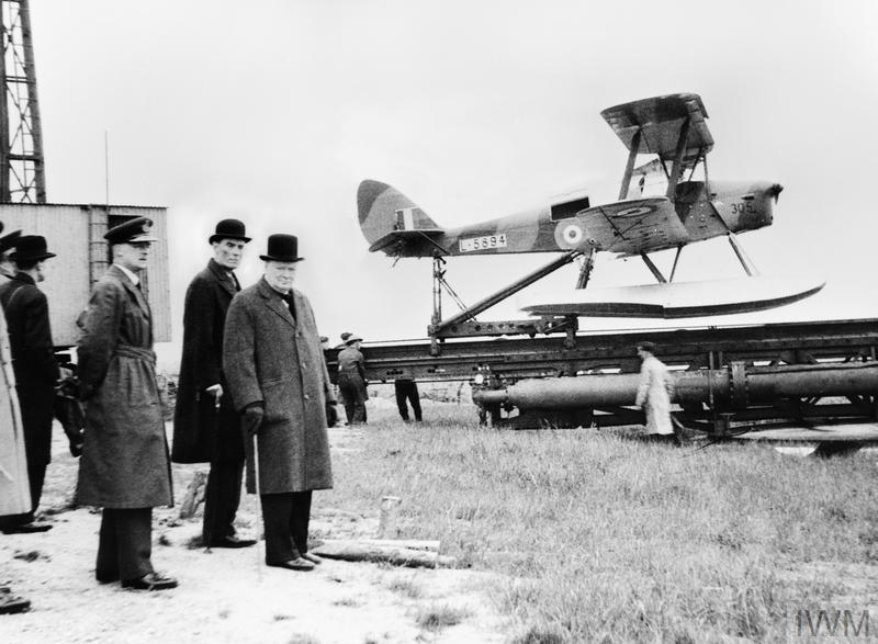 The Prime Minister, Mr Winston Churchill, with Captain The Right Honourable David Margesson, Secretary of State for War, watching preparations being made in an unspecified UK location for the launch of a De Havilland Queen Bee seaplane L5984 from its ramp. The Queen Bee pilotless target drone was a radio-controlled version of the Tiger Moth trainer.