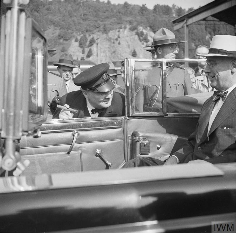 Churchill leaning into President Roosevelt's car to greet him after arriving for the Quebec conference in Canada, 11 September 1944.