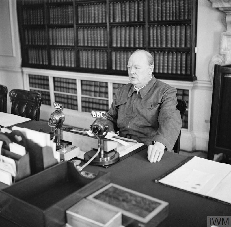 Winston Churchill makes a radio address from his desk at 10 Downing Street wearing his 'siren suit'.