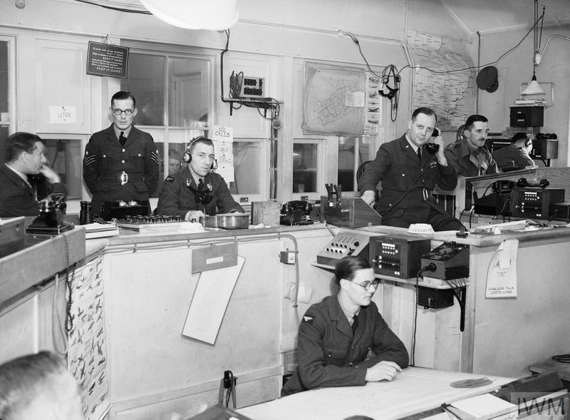 Interior of the Sector 'G' Operations Room at Duxford, Cambridgeshire. The callsigns of fighter squadrons controlled by this Sector can be seen on the wall behind the operator sitting third from left. The Controller is sitting fifth from the left, and on the extreme right, behind the Army Liaison Officer, are the R/T operators in direct touch with the aircraft.