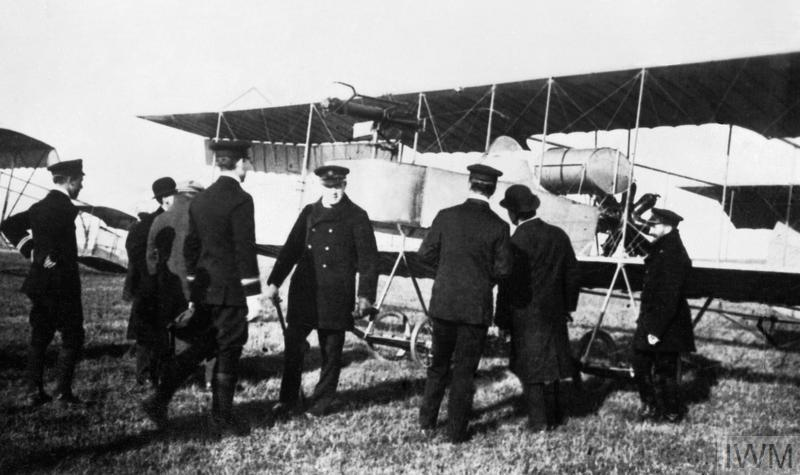 First Lord of the Admiralty, Winston Churchill (centre, facing camera), stands in front of Short Type S.38 Biplane (a.k.a. Short S.77), No. 66, of the Naval Wing of the Royal Flying Corps, during a visit to Eastchurch, Kent. No. 66, seen here with a Vickers Maxim gun fitted on the front of the gondola, was used for experimental gun and wireless installation tests at Eastchurch.