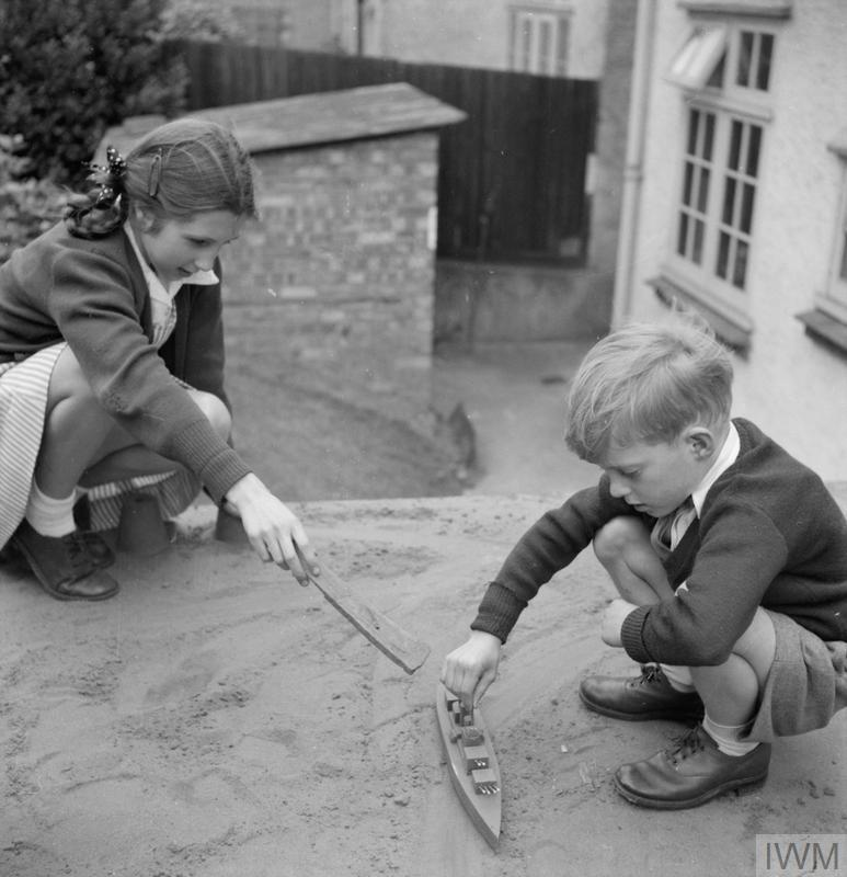 Two children play with a toy battleship