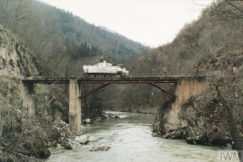 """""""Juliet"""", the Warrior IFV used by Colonel Bob Stewart, Commander of 1st Battalion, Cheshire Regiment, makes its way cautiously over an unsafe bridge at Malankovici. The Warrior is painted in the high visibility white colour scheme used to identify UNPROFOR vehicles in Bosnia."""