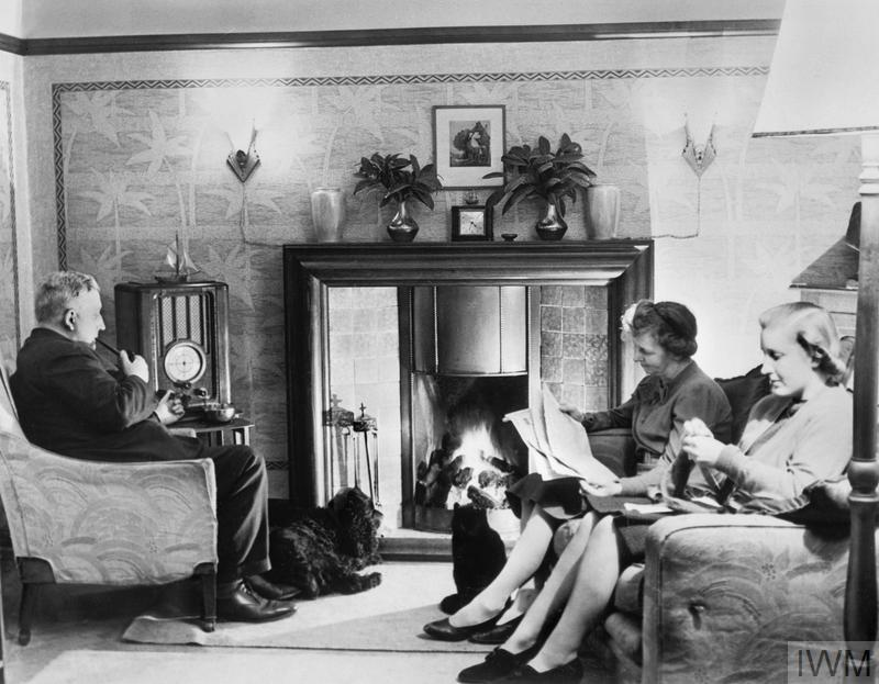 Home Front: A family relaxes at home on a Sunday afternoon in Taunton, Somerset, 1942. A man and two women occupy themselves with typical wartime leisure pursuits - reading, knitting and listening to the radio. A pet dog and cat sit by the fire.