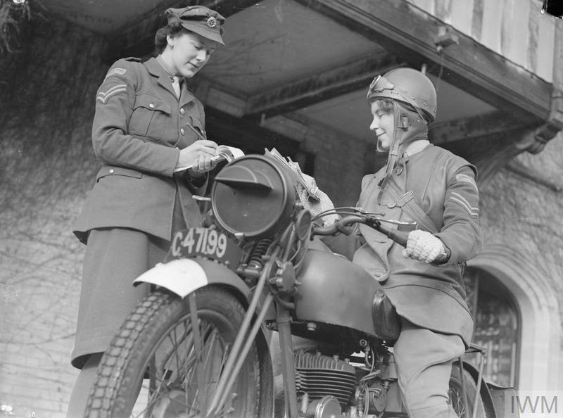 An ATS FANY Motorcycle Messenger sits on her motorbike as she receives her instructions from a FANY Corporal at the ATS MTC training centre, Camberley.