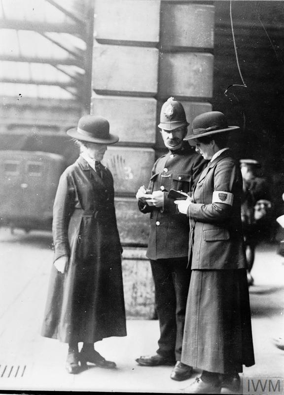 Two members of the Women's Police Service comparing notes with a male police constable at Euston Station, London, 1918.