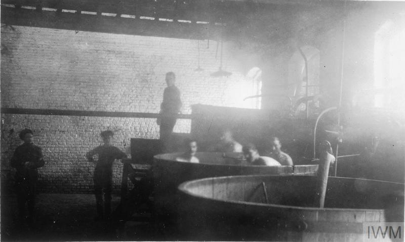 British soldiers washing in makeshift baths possibly near Armentieres, 1915.