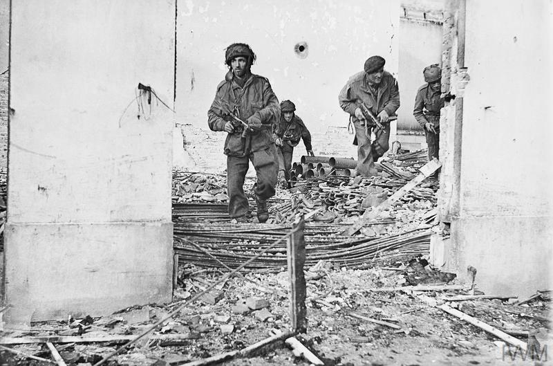 British airborne troops move through a shell-damaged house in Oosterbeek, 23 September 1944.
