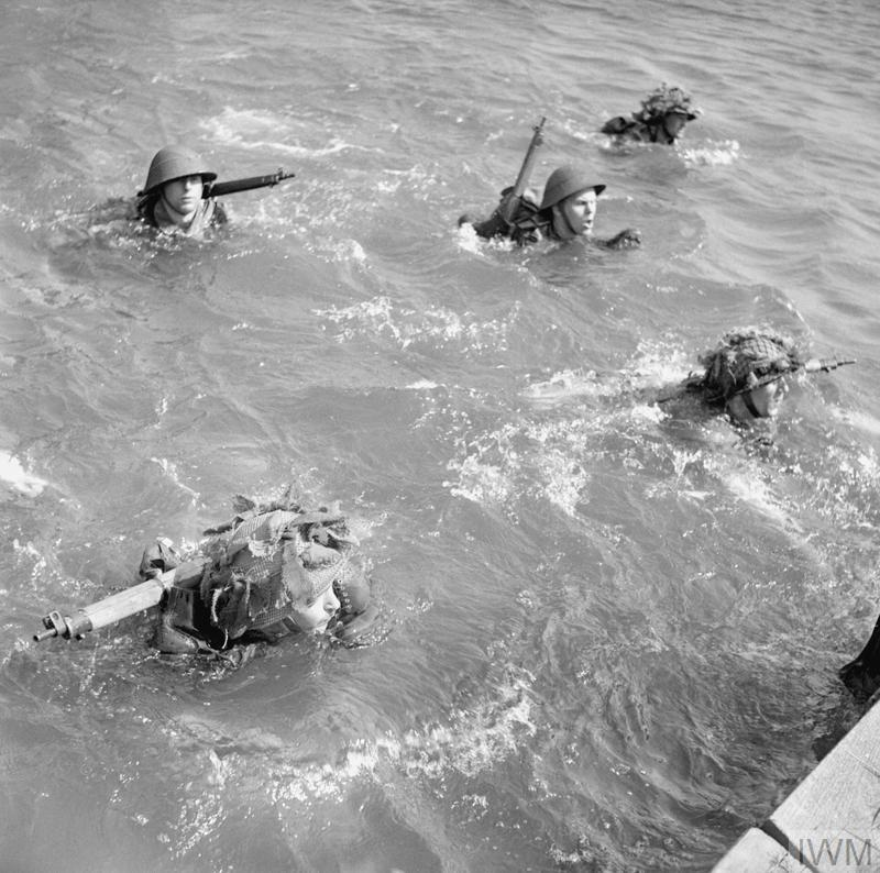 British troops learning to swim across a waterway in full kit on a physical training course for NCOs, 2 May 1944.