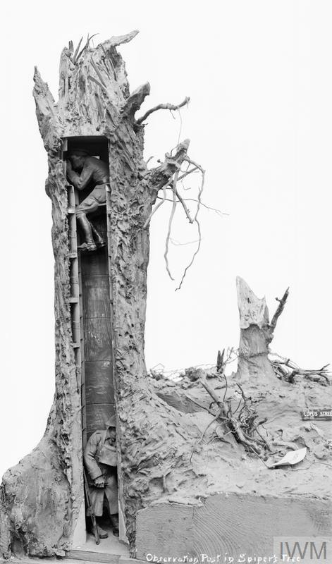 A model of a sectioned observation post with an artillery observer. The tower is disguised as a tree.