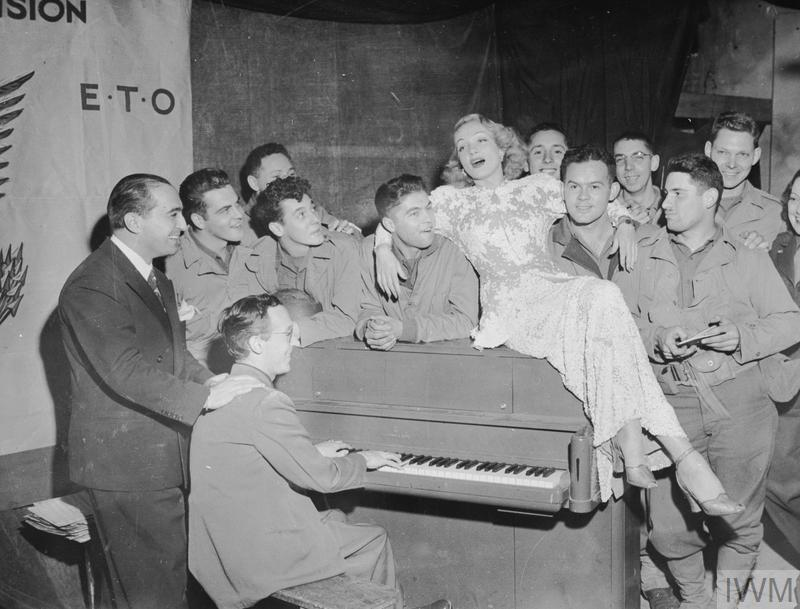 Wartime Entertainers: The actress and singer Marlene Dietrich during a concert in France. She is shown lounging on top of a piano surrounded by American soldiers. Although German by birth, Marlene Dietrich disassociated herself from Hitler's regime and devoted herself to supporting the morale of Allied troops.