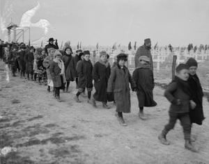 A group of Serbian refugee children wear overcoats, scarves and hats as they walk to the funeral of Mrs Harley (the sister of Lord French). Mrs Harley was killed by a shell at Monastir where she was organising relief for Serbians. SERBIAN REFUGEE CHILDREN, SALONIKA, 1917