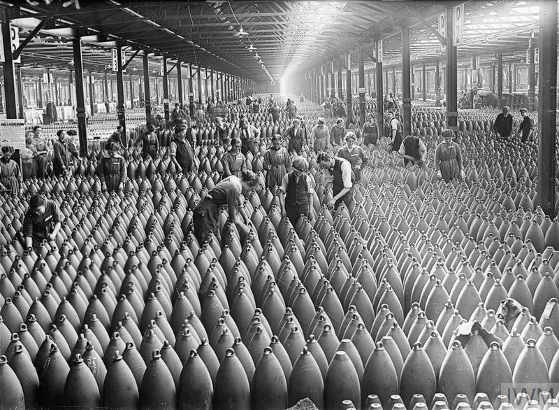 A general scene showing workers, both male and female, amid rows and rows of shells in a large warehouse at the National Filling Factory, Chilwell. August 1917