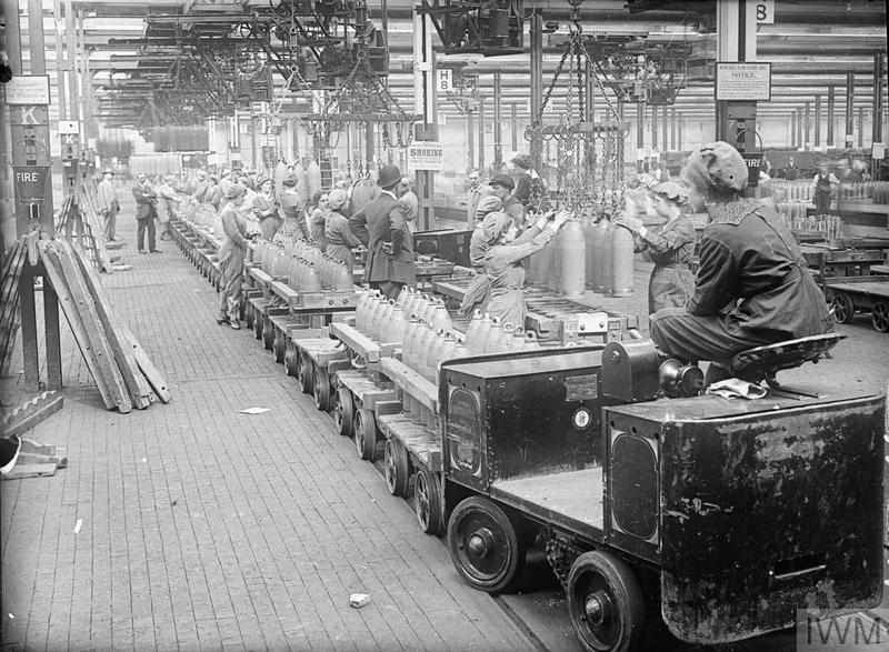 A woman drives a trolley train across a busy factory floor at the National Filling Factory, Chilwell. The trolley is loaded with shells and is used to transport the shells from one part of the factory to another. Around 21 August, 1917.